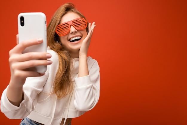 Nahaufnahmeporträt der attraktiven positiven lächelnden jungen blonden frau, die stilvollen weißen hoodie trägt und
