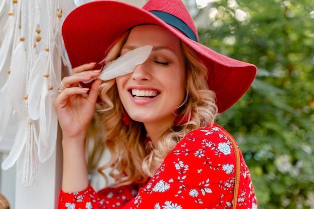 Nahaufnahmeporträt der attraktiven stilvollen blonden lächelnden frau im strohroten hut und im blusensommer-mode-outfit, das sexy sinnliche gesichtshaut der weißen feder hält