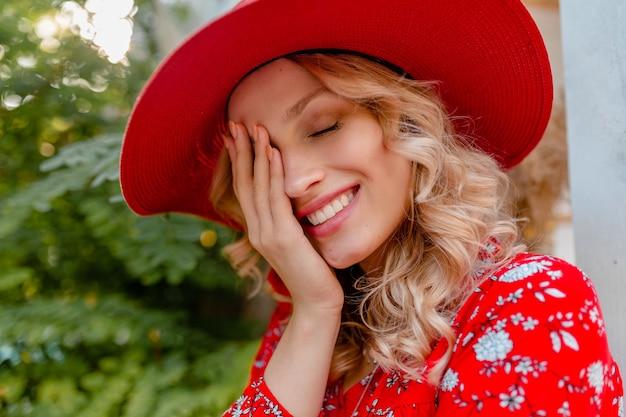 Nahaufnahmeporträt der attraktiven stilvollen blonden lächelnden frau im strohroten hut und im blusensommermode-outfit mit lächeln