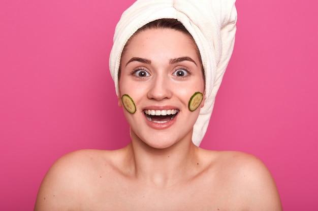 Nahaufnahmeporträt der beeindruckten zufriedenen lächelnden frau, die nackt über rosa steht