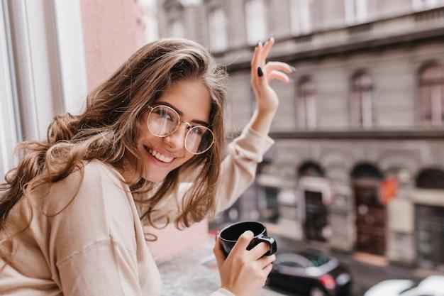Nahaufnahmeporträt der begeisterten jungen frau, die zeit nahe fenster mit tasse cappuccino verbringt