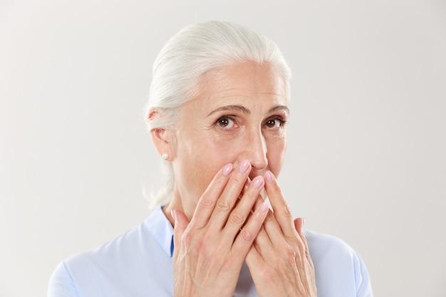 Nahaufnahmeporträt der bezaubernden alten dame, die ihren mund mit händen bedeckt