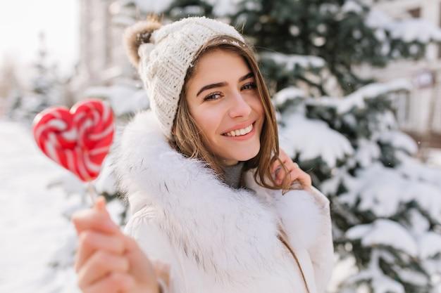 Nahaufnahmeporträt der bezaubernden dame im weißen mantel, der süßen lutscher hält. foto im freien der glückseligen blonden frau in der strickmütze, die neben baum am wintertag mit roter kandiszucker aufwirft.