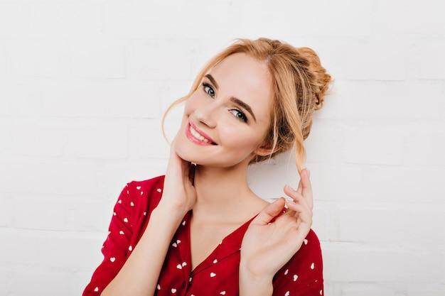 Nahaufnahmeporträt der blauäugigen erfreuten frau in der roten kleidung lokalisiert auf weißer wand. schönes kaukasisches mädchen mit blonden haaren, die sanft ihr gesicht berühren und lächeln