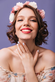 Nahaufnahmeporträt der blithesome frau mit trendiger maniküre und make-up. lächelndes liebenswertes mädchen im blumenkranz.