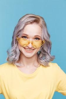 Nahaufnahmeporträt der blonden frau in der gelben kleidung und in den sonnenbrillen lokalisiert über dem blauen hintergrund.