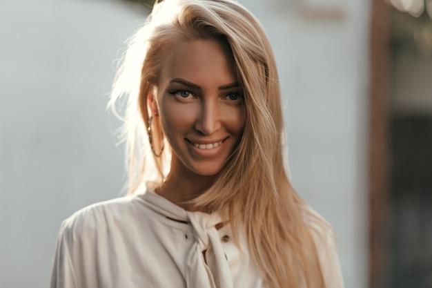 Nahaufnahmeporträt der blonden langhaarigen gebräunten frau in der weißen baumwollbluse, die nach vorne schaut, lächelt und draußen aufwirft Kostenlose Fotos