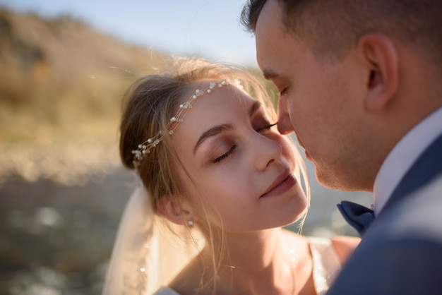 Nahaufnahmeporträt der braut und des bräutigams einen moment vor dem kuss.