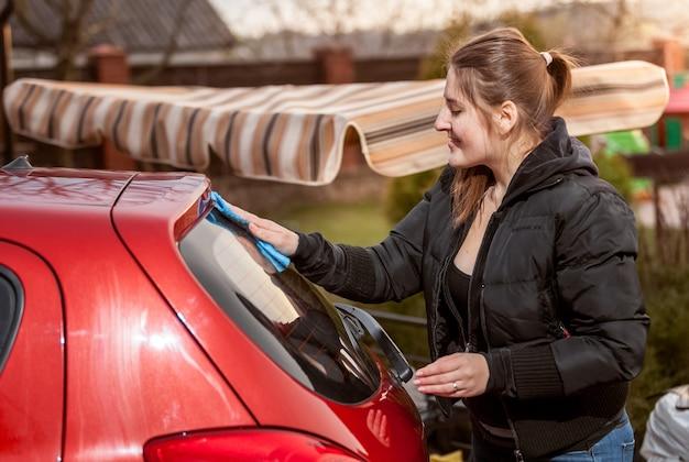 Nahaufnahmeporträt der brünetten frau, die rotes auto im freien wäscht