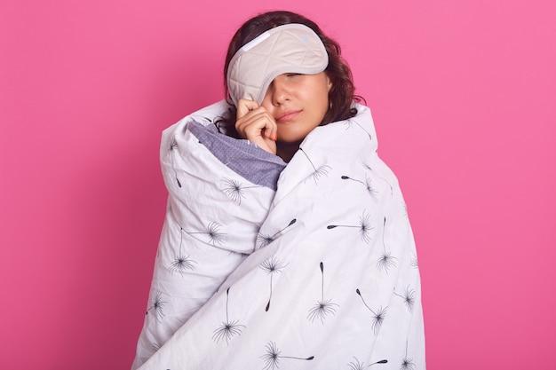 Nahaufnahmeporträt der brünetten frau, die von der schlafmaske guckt, nicht aufwachen will, augen geschlossen hält und weiße decke trägt