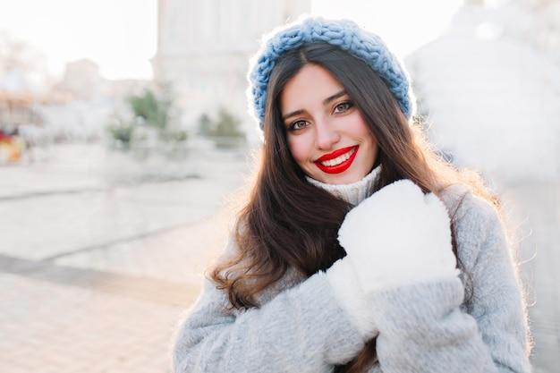 Nahaufnahmeporträt der brünetten frau mit den roten lippen, die auf unschärfestadt lächeln. foto im freien des sorglosen mädchens in der blauen strickmütze und in den warmen handschuhen, die mit überraschtem gesichtsausdruck aufwerfen.