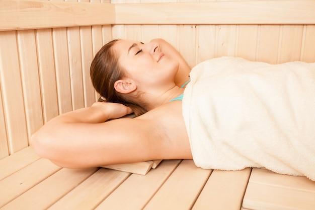 Nahaufnahmeporträt der brünetten frau mit handtuch bedeckt in der sauna liegend
