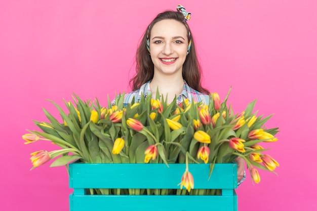 Nahaufnahmeporträt der brünetten jungen frau mit bündel tulpen auf rosa oberfläche