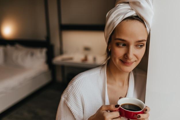 Nahaufnahmeporträt der charmanten dame im weißen bademantel und im handtuch, die im schlafzimmer mit tasse morgenkaffee aufwerfen.