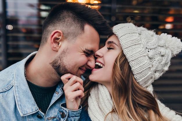 Nahaufnahmeporträt der debonair frau in der strickmütze, die spielerisch mit freund aufwirft. nettes europäisches paar, das an kaltem tag auf der straße herumalbert.