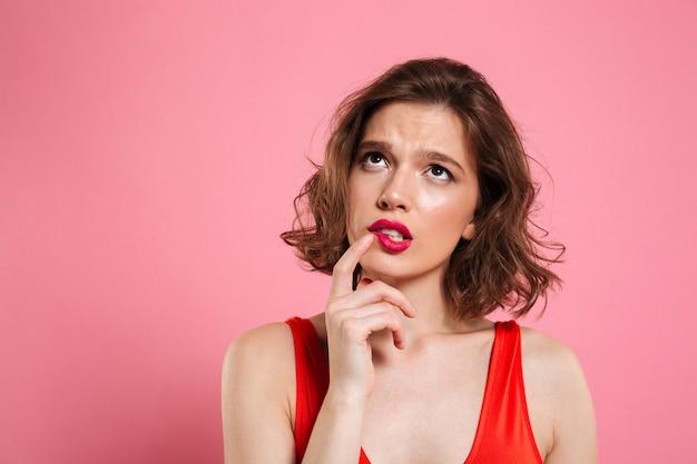 Nahaufnahmeporträt der denkenden jungen schönen frau mit den roten lippen, die mit dem finger ihre wange berühren und nach oben schauen