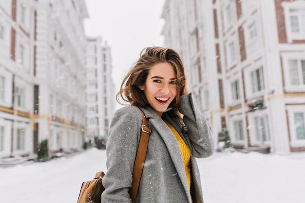 Nahaufnahmeporträt der ekstatischen frau im eleganten grauen mantel, der auf der straße im verschneiten tag steht. foto im freien des modischen weiblichen modells mit der braunen tasche, die durch stadt in den winterferien geht.