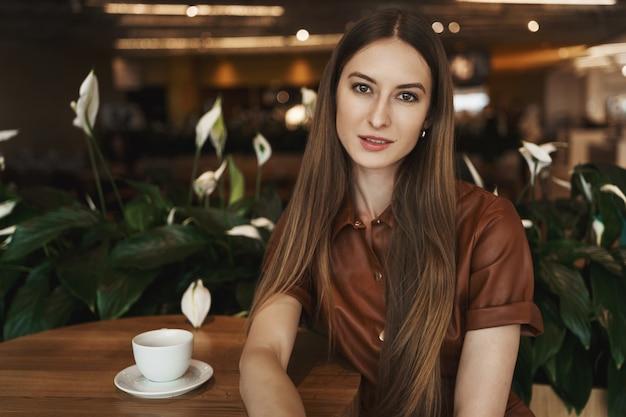 Nahaufnahmeporträt der eleganten charmanten jungen frau, die sich auf einen kaffeetisch in einem café stützt.