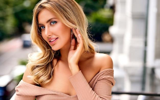 Nahaufnahmeporträt der eleganten frau. ohrringe, zubehör. schöne blonde frau mit langem lockigem haar mit schönheitsmake-up und weiblichem modeporträt der gesunden haut. das mädchen mit einem angenehmen lächeln.