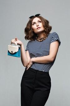 Nahaufnahmeporträt der eleganten sexy frau in einem kühlen hellen glamour-outfit, lippen, gestreiftes hemd und schwarze baggy-hose. , seemannsfrau, trendiges, lockiges haar, modehandtasche