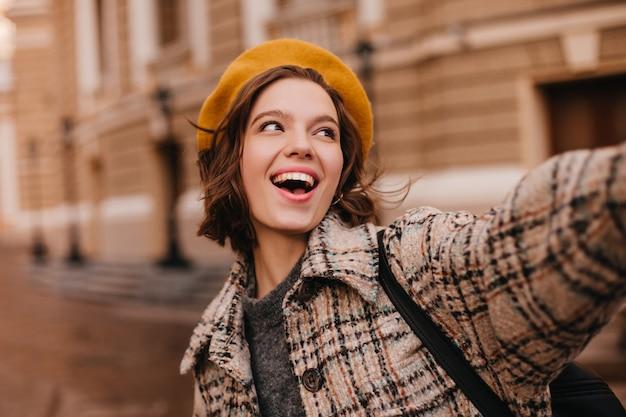 Nahaufnahmeporträt der emotionalen pariserin im mantel und in der baskenmütze