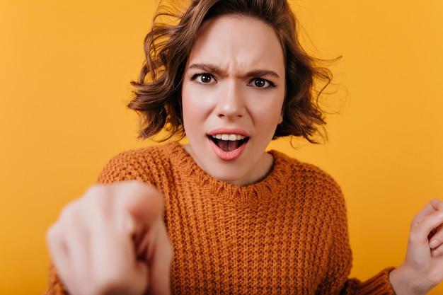 Nahaufnahmeporträt der enttäuschten jungen frau trägt leuchtend gelben pullover