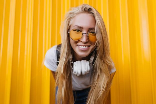 Nahaufnahmeporträt der entzückenden blonden frau in der niedlichen sonnenbrille.
