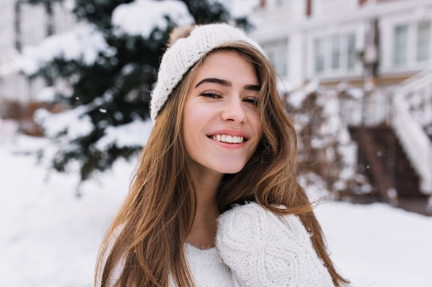 Nahaufnahmeporträt der erfreuten blonden frau mit aufrichtigem lächeln, das wintermorgen genießt. schöne europäische frau im weißen hut, der schneebedeckte ansicht im freien betrachtet.