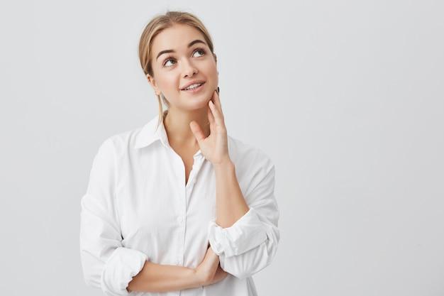 Nahaufnahmeporträt der erfreuten frau mit reiner haut, dunklen augen und aufrichtigem lächeln, das weißes hemd posierend aufwirft. verträumte frau, die über angenehme dinge nachdenkt und nach oben schaut.