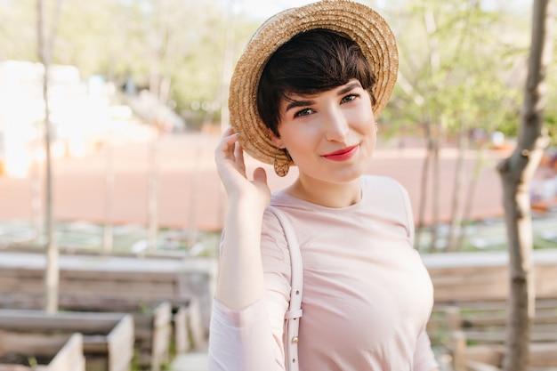 Nahaufnahmeporträt der erfreuten jungen frau mit dunkelbraunem haar und nacktem make-up