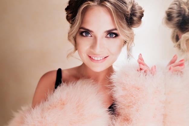 Nahaufnahmeporträt der erstaunlichen glücklichen künstlerin mit hollywood-lächeln, das in der umkleidekabine nach leistung steht. hübsche junge frau in der rosa flauschigen kleidung, die neben schminkspiegel aufwirft