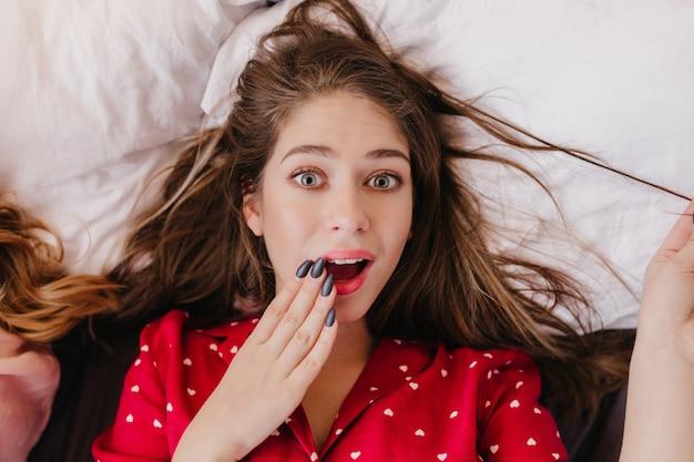 Nahaufnahmeporträt der erstaunlichen jungen frau trägt stilvolle rote pyjamas. innenüberkopfaufnahme des überraschten brünetten mädchens, das auf weißem kissen liegt.