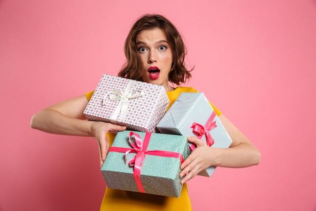 Nahaufnahmeporträt der erstaunten schönen frau, die bündel von geschenken hält,