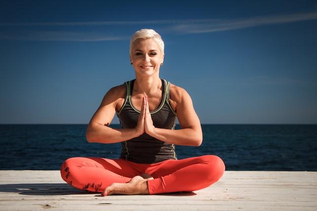 Nahaufnahmeporträt der erwachsenen blonden frau mit kurzem haarschnitt übt yoga auf dem pier vor dem hintergrund des meeres und des blauen himmels