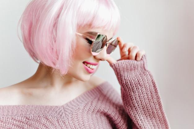 Nahaufnahmeporträt der faszinierenden kurzhaarigen dame in den gläsern, die auf lichtwand aufwerfen. weibliches modell in trendiger rosa perücke.