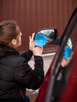 Nahaufnahmeporträt der frau, die autospiegel säubert