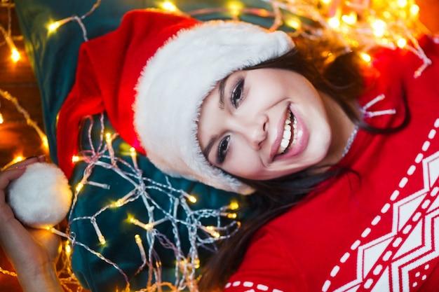 Nahaufnahmeporträt der frau eingewickelt in den weihnachtslichtern, die zu hause auf boden liegen