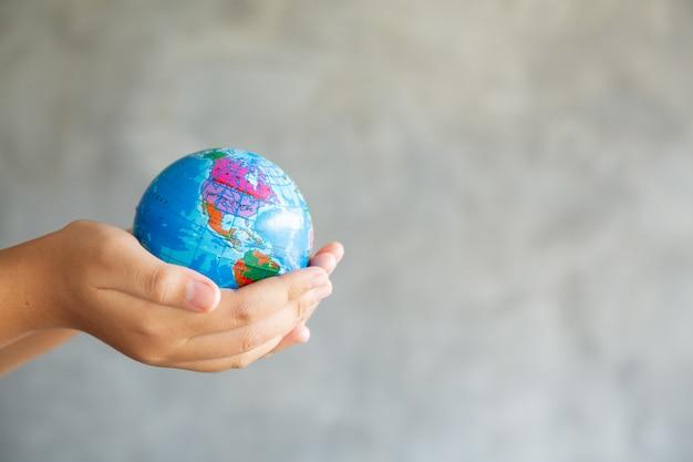 Nahaufnahmeporträt der frau hält global in ihren händen auf grau