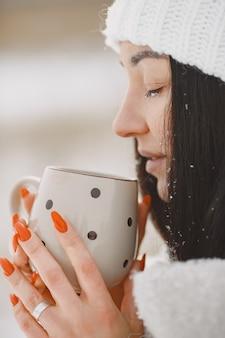 Nahaufnahmeporträt der frau im weißen pullover mit tee