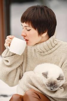Nahaufnahmeporträt der frau im weißen pullover mit weißer katze, trinkenden tee