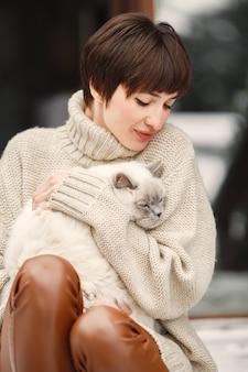 Nahaufnahmeporträt der frau im weißen pullover mit weißer katze
