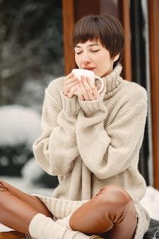 Nahaufnahmeporträt der frau im weißen pullover, tee trinkend