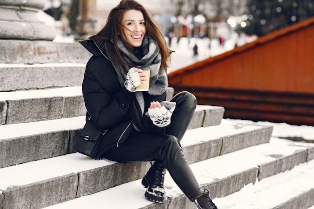 Nahaufnahmeporträt der frau in der schwarzen jacke mit kaffee zum mitnehmen