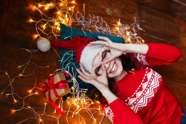 Nahaufnahmeporträt der frau in sankt-hut eingewickelt in den weihnachtslichtern, die spaß haben und auf boden liegen