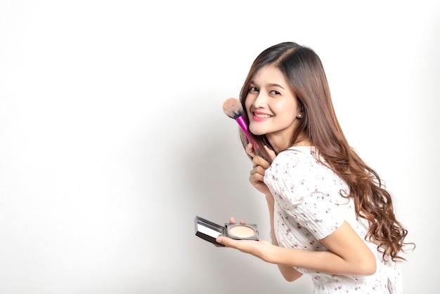 Nahaufnahmeporträt der frau mit make-up-pinsel nahe gesicht auf weißer wand