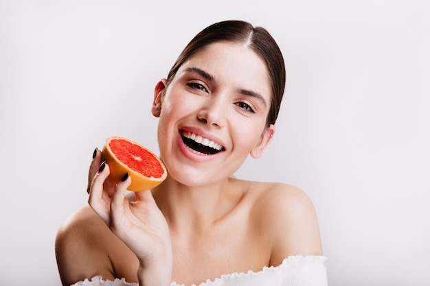 Nahaufnahmeporträt der frau mit perfekter sauberer haut und schneeweißem lächeln. modell posiert mit roten saftigen zitrusfrüchten.