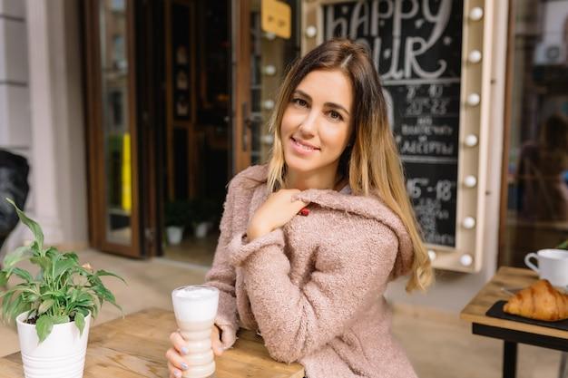 Nahaufnahmeporträt der frau sitzt auf der straße und trinkt kaffee