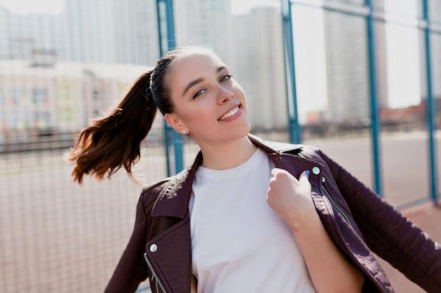 Nahaufnahmeporträt der freudigen lachenden jungen dame gekleidete lederjacke und des weißen hemdes