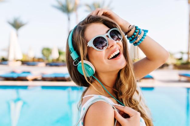 Nahaufnahmeporträt der freudigen lachenden jungen dame in den trendigen armbändern, die mit hand oben nahe dem blauen schwimmbad im freien aufwerfen