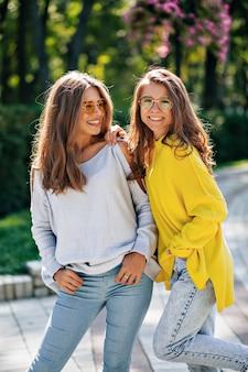 Nahaufnahmeporträt der freundlichen glücklichen mädchen mit dem aufstellen in hellen gläsern außerhalb. zwei junge damen mit schönem gesichtsausdruck verbringen zeit miteinander